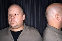 Caucasian mid adult bald man looking away from his identical twin