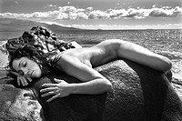 Nude Caucasian mid adult woman draped over rock with at coast in background