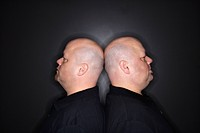 Caucasian mid adult identical twin bald men standing back to back