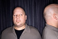 Caucasian mid adult bald man looking to side at his identical twin