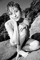 Mid adult nude Caucasian woman crouching on rock looking at viewer