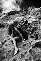 Young Asian nude woman sitting in a crevice in a rock.