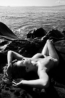 Sexy Caucasian young adult woman sunbathing nude on rocks at coast
