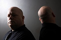 Caucasian mid adult bald identical twin men standing back to back and looking at viewer
