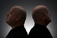 Caucasian mid adult bald identical twin men standing back to back