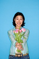 Half length portrait of pretty Asian mid adult woman holding flowers on blue background