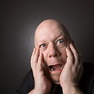 Caucasian mid adult bald man with hands to face making scared facial expression