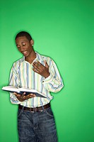 Portrait of African-American teen boy reading book standing in front of green background (thumbnail)