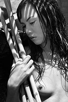 Close up of young nude multiethnic woman holding bamboo
