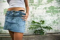 Torso shot of Caucasian mid_adult blonde woman wearing blue jean mini skirt with underwear showing beside building in alley