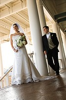 Caucasian mid_adult fbride and groom standing on porch