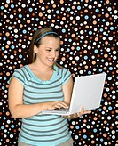 Young Caucasian woman typing on laptop and smiling (thumbnail)