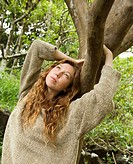 Caucasian young adult woman in lush forest holding onto tree branch and looking up (thumbnail)