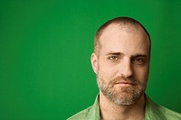 Head shot of Caucasian man with beard and receding hairline against green background