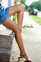 Legs of Caucasian mid-adult woman wearing blue jean skirt and heels (thumbnail)