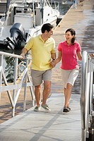 Mid_adult Caucasian couple holding hands and walking up ramp at harbor