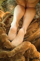Caucasian mid adult female legs kneeling on fur blankets