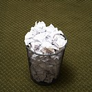 Wire mesh trash can filled with crumpled paper on green carpet