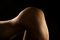 Nude Hispanic mid adult woman bending over at waist