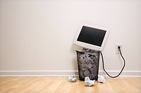 Computer monitor in trash can surrounded by crumpled up paper