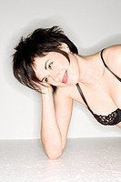 Close-up of young sexy Caucasian woman wearing black lace bra lying on the floor and smiling (thumbnail)