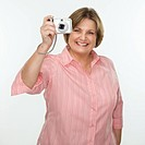 Caucasian middle aged woman taking photo with digital camera of viewer