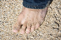 Close up of mid-adult Caucasian male foot wearing jeans on sandy beach (thumbnail)