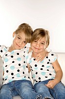 Female children Caucasian twins sitting together on chair