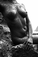 Young adult Caucasian female nude sitting on rocky coast