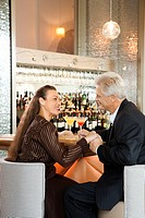 Caucasian mature adult male and prime adult female sitting at bar holding hands