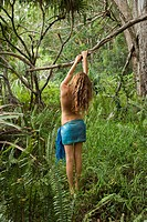 Topless Caucasian young adult woman wearing blue sarong in lush forest of ferns holding on to tree branch over head.l