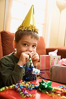 Boy at birthday party looking at viewer blowing noisemaker