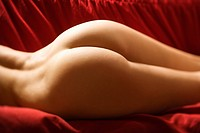 Derriere of sexy nude Caucasian young adult female lying seductively on red couch