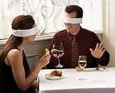 Mid adult Caucasian couple dining in a restaurant with blindfolds over eyes