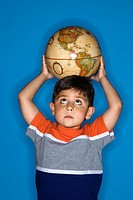 Male Hispanic boy holding globe on head