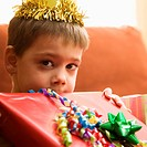 Caucasian boy holding gift up to face and looking at viewer