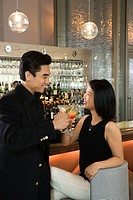 Prime adult Asian male and female at bar with cocktails