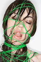 Nude Caucasian young adult woman wrapped in string licking lips (thumbnail)