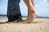 Feet and legs of mid_adult Caucasian couple standing together on beach