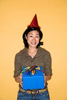 Pretty mid adult Asian woman wearing party hat holding present