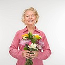 Caucasian senior woman holding bouquet of flowers and smiling at viewer