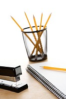 Pencils, a stapler, and spiral bound notebooks arranged on a desk (thumbnail)