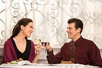 Mid adult Caucasian couple smiling and toasting wine glasses in restaurant