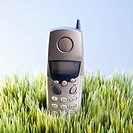 Studio shot of landline telephone placed in grass