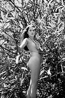 Nude young adult woman standing amongst branches and leaves looking at viewer