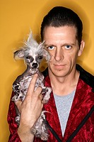 Caucasian mid_adult male wearing velvet and holding Chinese Crested dog