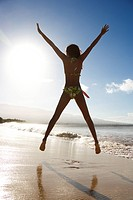 Girl in bikini jumping on beach