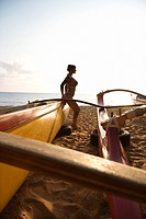 Silhouette of sexy Caucasian woman in bikini beside outrigger canoe on beach