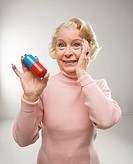Caucasian senior woman holding oversized pill at viewer