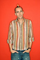 Caucasian man with mohawk standing against red background